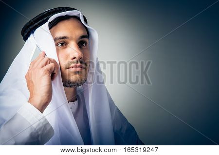 studio shot of young man wearing traditional arabic clothing, talking on the phone