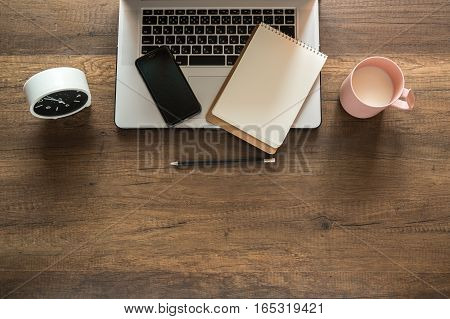 Working place, Laptop, Memo, Clock, Coffee cup on wooden background.