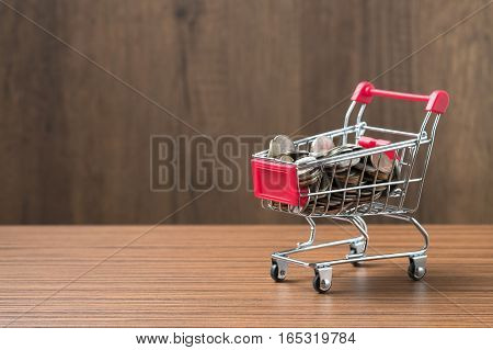 Saving and shopping concept. Coins on shopping cart.