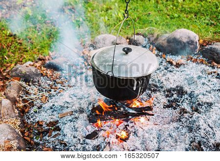 Metal pot over a campfire outdoors. Cooking food at a camping trip.
