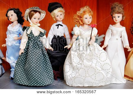 set of different beautiful dolls standing on the shelf