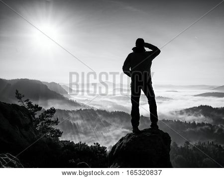 Autumnal  Misty Morning In Nature. Hiker In Black Stand On Peak In Rock