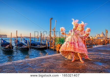 Famous Carnival Masks Against Gondolas In Venice, Italy
