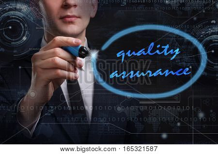 Business, Technology, Internet And Network Concept. Young Business Man Writing Word: Quality Assuran