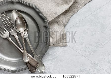 Various silverware on a pewter plate and gray flax napkin are on the background of gray concrete surface with copy-space