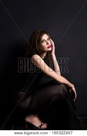 A brunette woman wearing a black dress and sandals sits on a black background