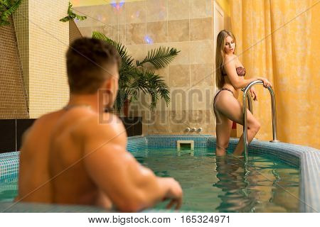 Young beautiful romantic couple relaxing together in jakuzzi at spa resort