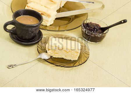Piece of layered sponge cake on a glass saucer with spoon on the background of the rest of the cake coffee with milk in a black cup and jam on a cloth surface