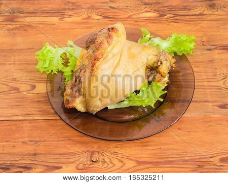 Baked ham hock with lettuce on a glass dish on a surface of old wooden planks