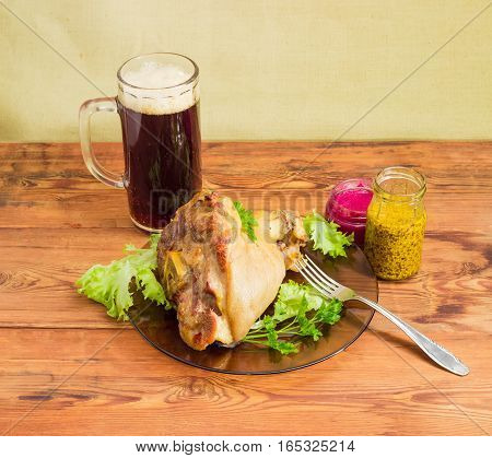 Baked ham hock with lettuce and parsley on a glass dish glass of dark beer beet horseradish sauce French mustard and fork on a surface of old wooden planks