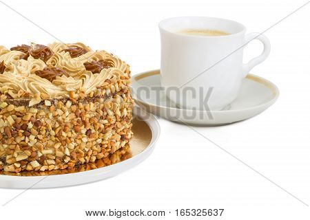 Fragment of a round sponge cake decorated with butter cream and caramelized condensed milk sprinkled with grated nuts on a background of white cup with coffee with cream on a light background