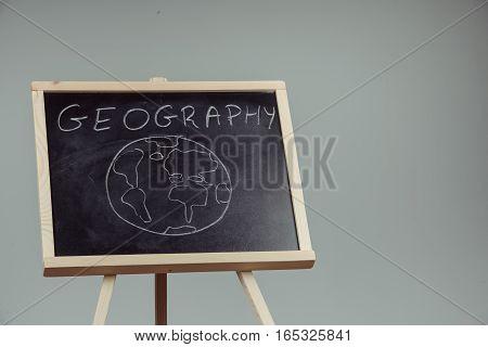 Geography Lesson On Blackboard Or Chalkboard. Written In White Chalk