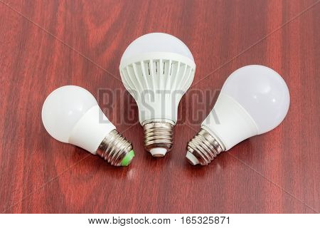 Three different domestic light emitting diode lamp with a sized E27 male screw base on a dark wooden surface