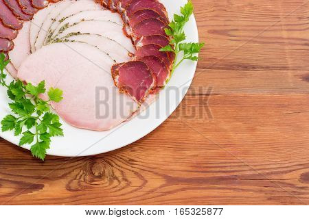 Fragment of white dish with sliced dried pork tenderloin ham and twigs of parsley closeup on a light background