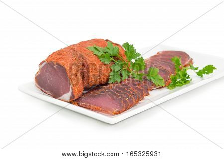 One piece and sliced dried pork tenderloin with twigs of parsley on a white rectangular dish closeup on a light background