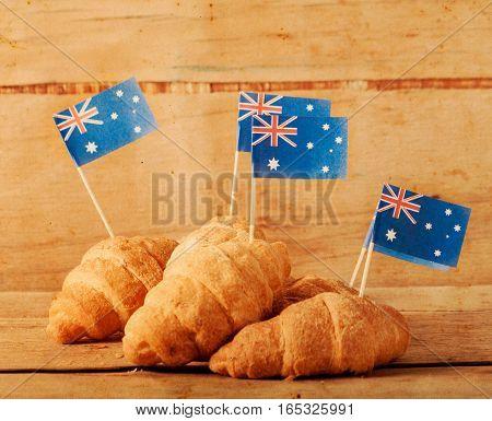 Fresh croissant and australian flag on wood desk. Greeting card