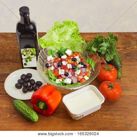 Greek salad in a glass salad bowl among ingredients for its cooking on an old wooden surface