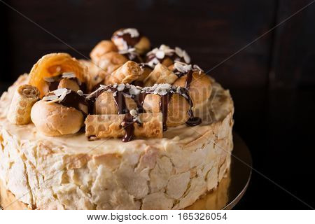 Napoleon cake on a dark wooden background decorated with petals of almonds eclairs waffles and chocolate icing