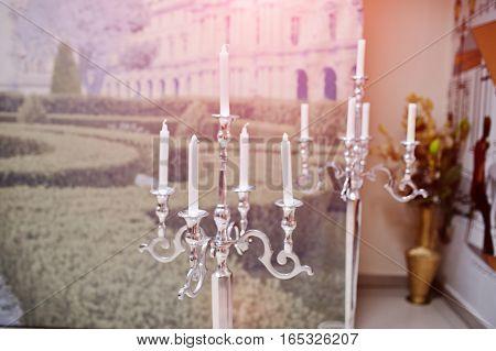 Silver vintage metal candlesticks on wedding hall.
