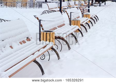 Rows of park benches made of forged steel frame and wooden planks and covered with snow in a public garden on a cloudy day