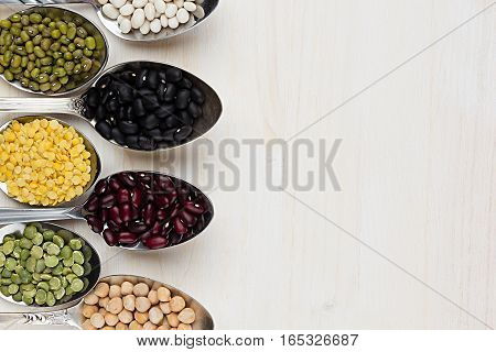 Assortment legume beans in spoons with copy space on white wood background. Top view closeup.