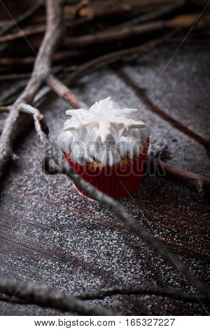 Chocolate cupcakes with white butter cream decorated withstarson a dark wooden background.