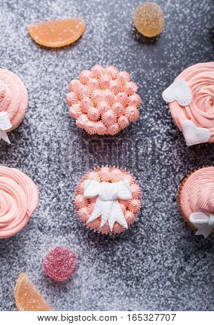 Pink cupcakes on a dark background with flour top view pink cream