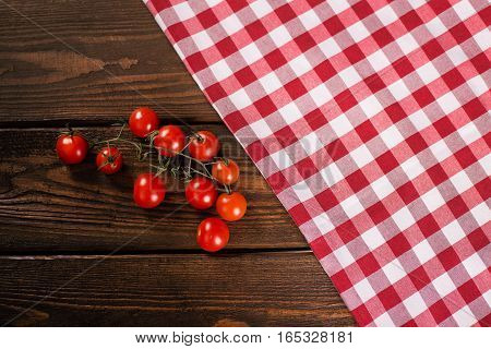 Cherry tomatoes in a red tablecloth cell on a wooden background