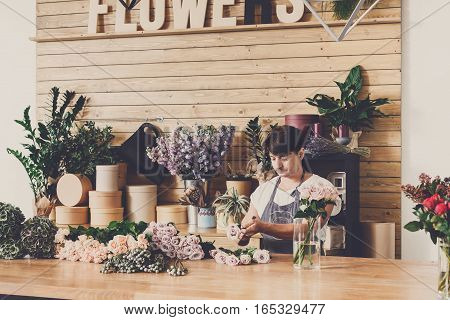 Small business. Male florist making rose bouquet in flower shop. Man assistant or owner in floral design studio, making decorations and arrangements. Flowers delivery, creating order. Filtered