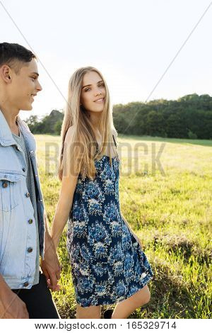 Couple runs in the wheat field and smiling. Young beautiful couple poses on nature in field. series.Сouple outdoor.Young stylish fashion couple posing in summer in field. Valentine's Day concept
