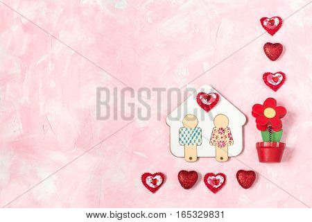 Festive composition to Valentines Day. Symbol of love and fidelity - hand-painted wooden house with little man flower and hearts on a pink textured background with space for text. Flat lay top view