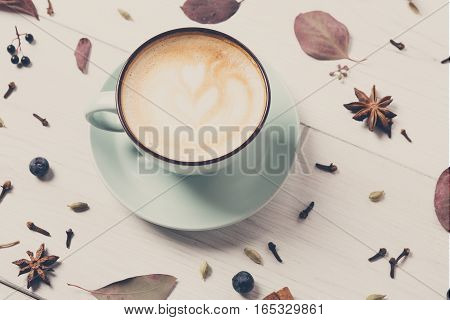 Spicy cappuccino composition. Blue coffee cup with foam, cloves, cinnamon, herbs and spices on white wood background. Creative hot drinks, cafe and bar concept