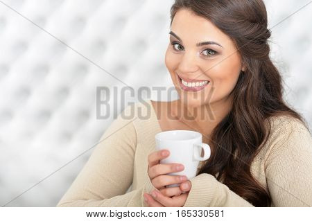 Portrait of a woman drinking tea in light room