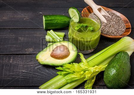 Healthy green juice smoothie surrounded by avocado, cucumber,  celery and chia seeds on black wooden background, top view