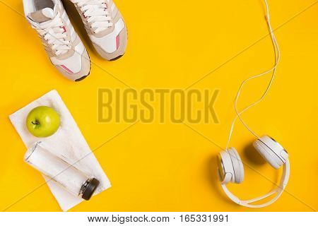 Athlete's set with female clothing, headphones and bottle of water on yellow background. Top view. Still life