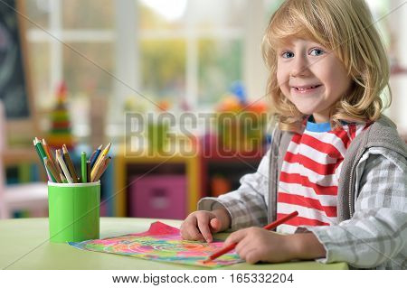 Portrait of smiling little boy with long blond hair drawing