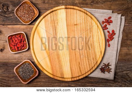 Flax and chia seeds and goji in a wooden bowls on wooden background, healthy superfood, top view