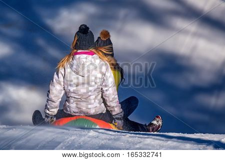 Girls sledding down a snowy hill on a color inflatable tube