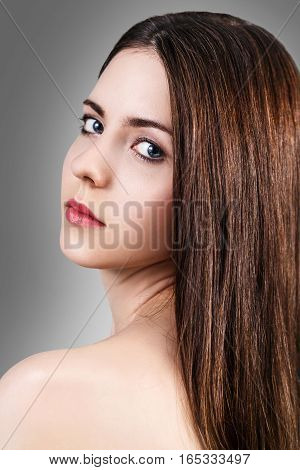 Young beautiful woman with healty fresh skin looking around over gray background. Spa concept.
