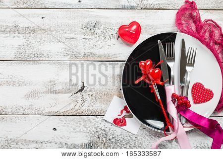 Valentine's day table setting. Table set with plate, knife and fork on white wooden background. Top view and copy space. Love concept.