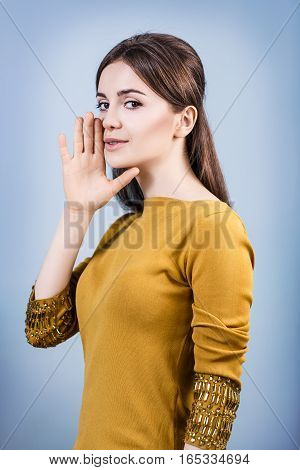 Young teenage woman whispering over blue background