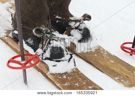 Old hand made wooden skis and human feet wearing warm boots with rubbers, cropped closeup shot