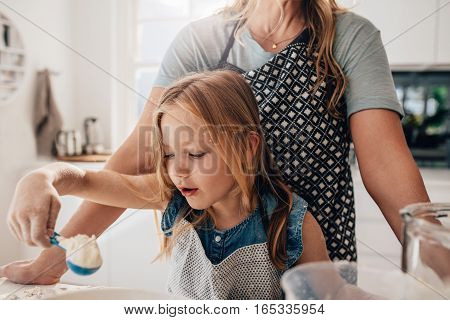 Little girl mixing batter in kitchen with her mother standing at the back. Girl learning baking with her mother. Adding flour in the bowl.