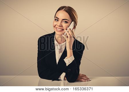 attractive dark-haired woman dressed in a black suit is sitting at a table in an office. Secretary looking at the camera and talking on the phone
