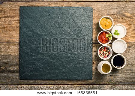 bowls of various dip sauces on wooden background, top view with copy space