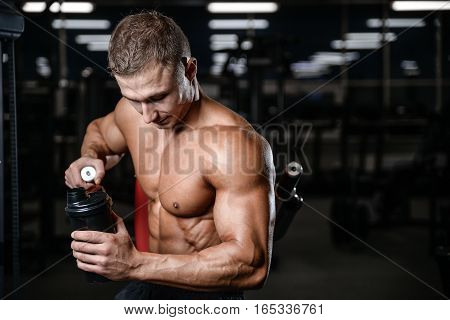 Handsome Fitness Model Holding A Shaker In The Gym Gain Muscle.