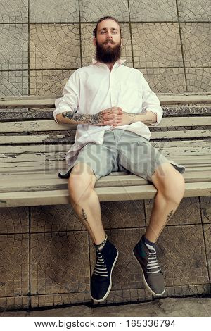 Cool Looking Guy With Tatoos And Long Beard Sitting On Chair
