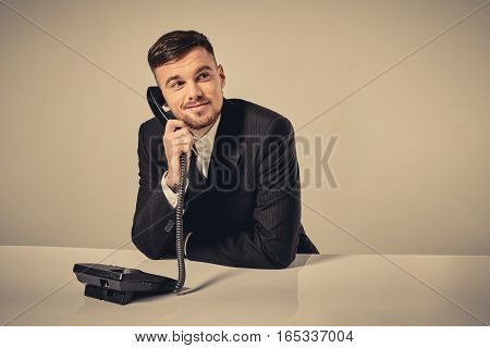 A young man in a black suit dials the phone number while sitting in the office. Manager talking on the phone