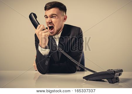A young man in a black suit dials the phone number while sitting in the office. Manager talking on the phone. Man emotionally shouts