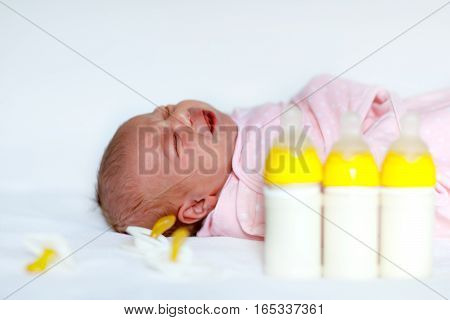 Hungry newborn baby girl with nursing bottles and pacifier. Formula drink for babies. New born child, little girl laying in bed. Family, new life, childhood, beginning, bottle-feeding concept.